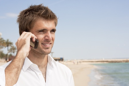 young businessman talking on the mobile phone at the beach Фото со стока