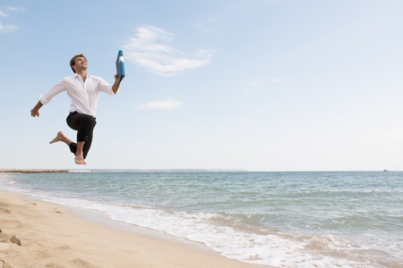 happy young businessman is running on the beach