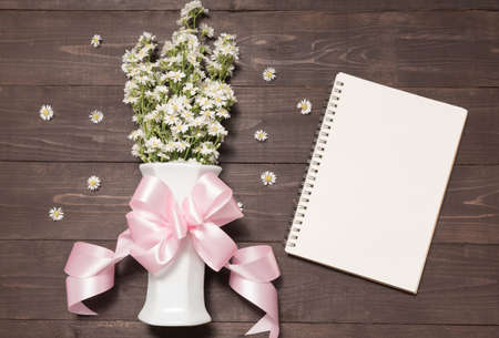 spacial: Cutter flowers with ribbon are in the vase beside of notebook.