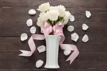 white space: White roses flower with ribbon are in the vase.