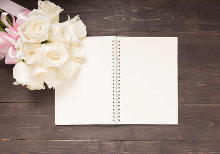 white space: White roses flower with ribbon are on the notebook