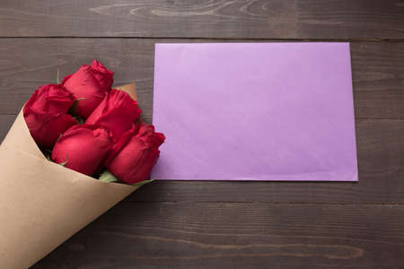 spacial: Red roses flower with the card are on the wooden background. Stock Photo