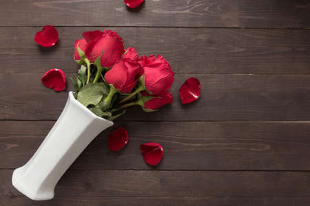 spacial: Red roses flower are in the white vase on the wooden background.