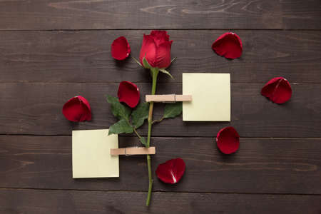spacial: Red rose flower is on the wooden background with sticky note.