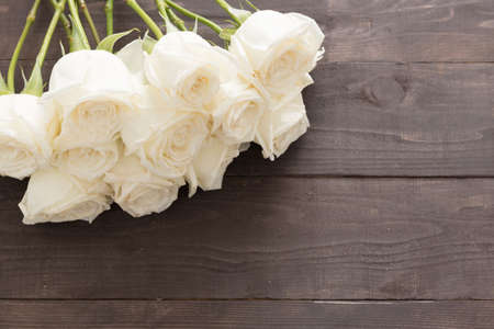 spacial: White roses are on the wooden background.
