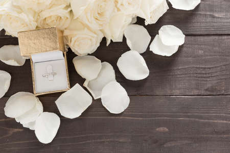 spacial: Ring is beside of white roses flower are on the wooden background. Stock Photo