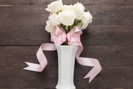 spacial: White roses flower with ribbon are in the vase.