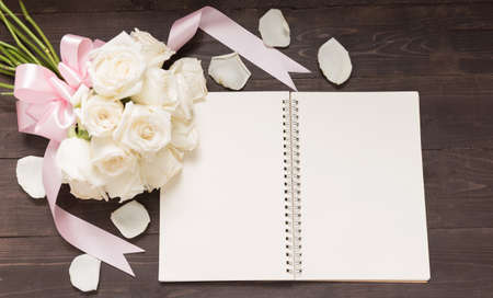 spacial: White roses flower with ribbon are on the notebook