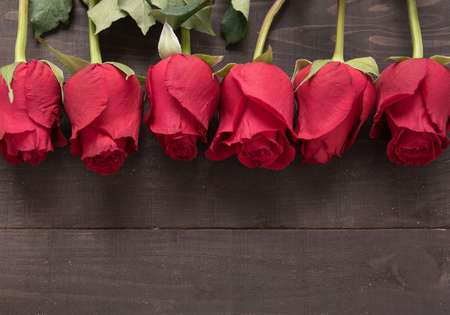 spacial: The arrangement of red roses flower on the wooden background. Stock Photo