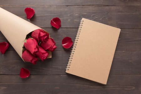 spacial: Red roses flower with the notebook are on the wooden background. Stock Photo
