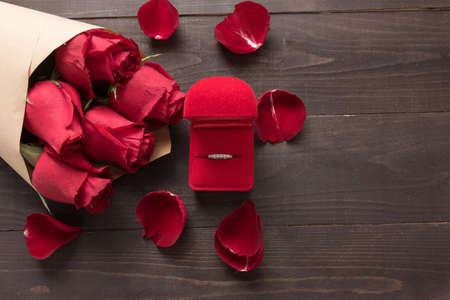 spacial: Ring is beside of the red roses flower on the wooden background.