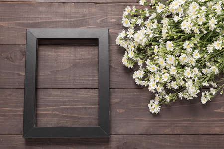 spacial: Picture frame and cutter flowers are on the wooden background. Stock Photo