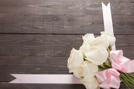 spacial: White roses flower with ribbon are on the wooden background.