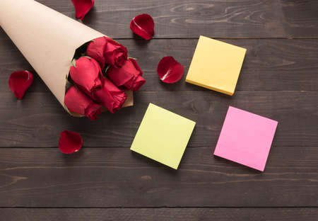 spacial: The arrangement of red roses flower with sticky notes are on the wooden background. Stock Photo