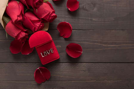 spacial: Love is beside of the red roses flower on the wooden background. Stock Photo