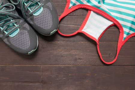 activewear: Sneakers and activewear are on the wooden background.