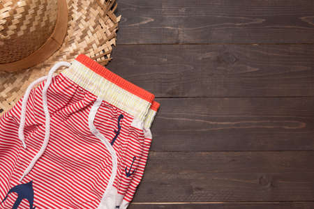 swimming shorts: Swimming shorts and hat is on wooden background.