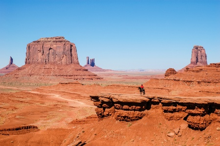 an Indian on a horse in front of a red rock formations in Monument Valley, USA