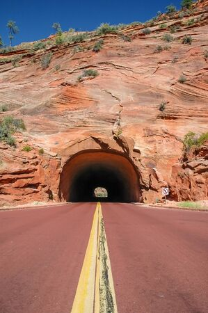 Red road that leads into a tunnel in Zion National Park, Utah, USA photo