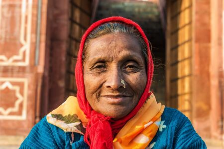 An old woman with a nose ring and a red scarf in Delhi, India