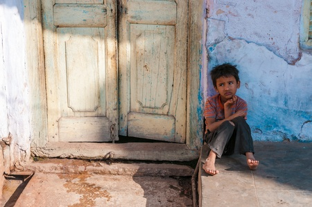 An Indian boy sits in front of a doorway, Pushkar, Rajasthan, India