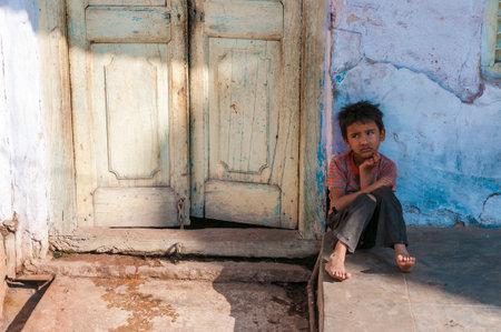 gente pobre: Un muchacho indio se sienta delante de una puerta, Pushkar, Rajasthan, India