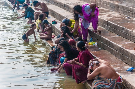 Indian people wash themselves in the river Ganges in Varanasi, India