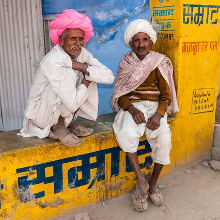 Two old Indian man with colorful turban in front of a shop, Rajasthan, India Stock Photo