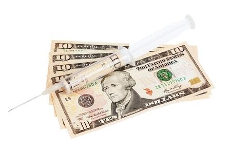 Syringe containing a ten dollar bill resting on some ten dollar bills Stock Photo