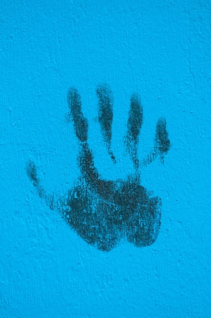 Palm print in black in a blue painted wall  photo