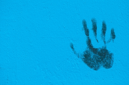 Palm print in black in a blue painted wall with copy-space