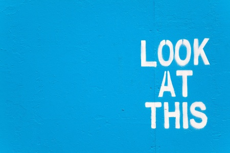 White stencilled graffiti on a blue painted wall with the words  Look At This photo
