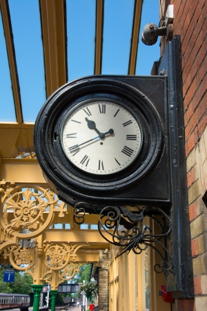 Antique style railway station clock wall mounted with platform in the background