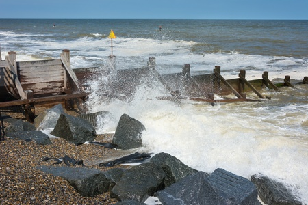 coastal erosion: Groynes to prevent coastal erosion with waves breaking onto a shingle beach.