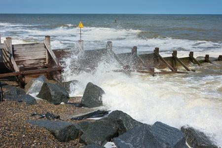 groyne: Groynes to prevent coastal erosion with waves breaking onto a shingle beach.