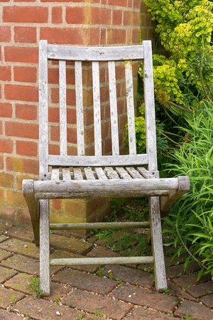 An old faded garden chair in the corner of a garden