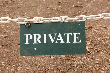 A Private property sign suspended on a white chain forming a barrier  photo