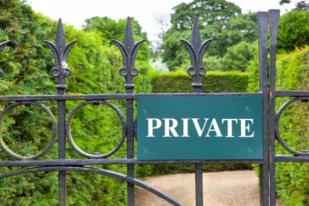Private sign attached to an ornate wrought iron gate leading into a garden