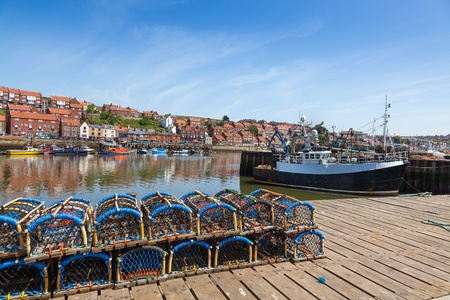 Whitby fishing harbor with lobster pots lining the quay  photo