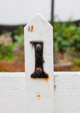 White garden gate post with the number one in black photo