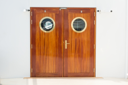 Double doors wiht brass fittings with a white wall background photo