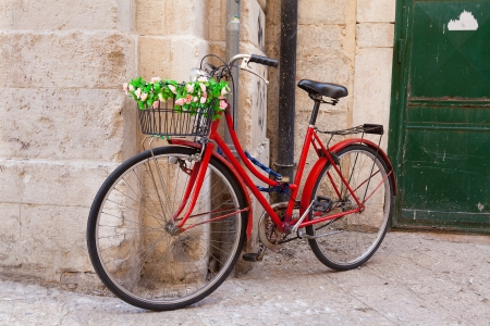 Old bicycle with basket decorated with flowers against a stone wall photo