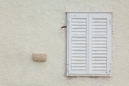 Shuttered white wooden window set in a plain wall