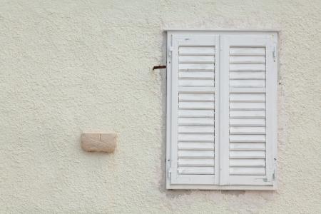 Shuttered white wooden window set in a plain wall Banco de Imagens - 23857446
