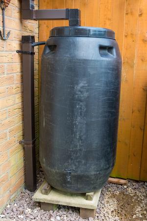 Black plastic water-butt for saving rainwater Stock Photo