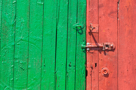 hasp: Weathered red and green painted wooden shed door. Stock Photo