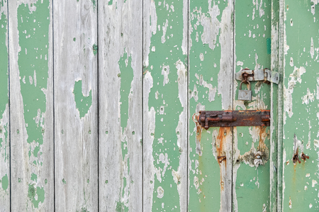 Weathered wooden door peeling green paint with rusty bolt and lock photo