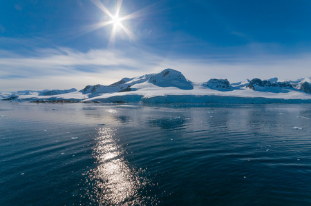 Paradise Bay Antarctica ocean and mountain view sun lens flare