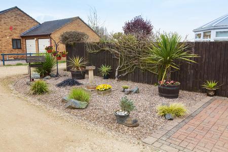 cordyline: Rockery garden in urban setting. Stock Photo