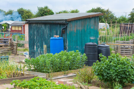 composting: Garden shed with compost and water bins